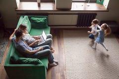 Ευτυχή παιδιά που παίζουν μαζί ενώ γονείς που χρησιμοποιούν το lap-top, τοπ άποψη στοκ εικόνα με δικαίωμα ελεύθερης χρήσης