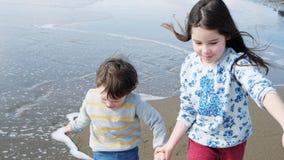 Ευτυχή παιδιά που παίζουν στην παραλία Αδελφή και αυτή χέρια λίγης αδελφών εκμετάλλευσης τρεξίματος απόθεμα βίντεο