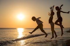 Ευτυχή παιδιά που παίζουν στην παραλία στο χρόνο ηλιοβασιλέματος στοκ εικόνα