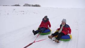 Ευτυχή παιδιά που το χειμώνα στο χιόνι και που κυματίζουν τα χέρια τους τα παιδιά γελούν και χαίρονται παιχνίδι κοριτσιών το χειμ απόθεμα βίντεο