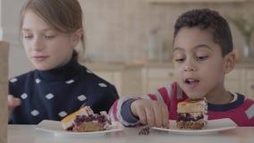 Ευτυχή παιδιά που τρώνε το κέικ καθμένος στον πίνακα στην κουζίνα απόθεμα βίντεο