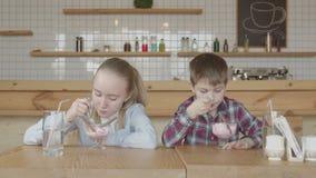Ευτυχή παιδιά που τρώνε το παγωτό με το gusto στον καφέ απόθεμα βίντεο