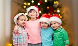 Ευτυχή παιδιά στα καπέλα santa που αγκαλιάζουν στα Χριστούγεννα στοκ εικόνες με δικαίωμα ελεύθερης χρήσης