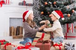 Ευτυχή παιδιά στα καπέλα santa που τα χριστουγεννιάτικα δώρα Στοκ φωτογραφίες με δικαίωμα ελεύθερης χρήσης