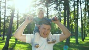 Ευτυχή παιχνίδια πατέρων με τη μικρή κόρη του στους ώμους στο ηλιοφώτιστο θερινό πάρκο φιλμ μικρού μήκους