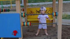 Ευτυχή παιχνίδια λίγων όμορφα αγοριών στην παιδική χαρά απόθεμα βίντεο