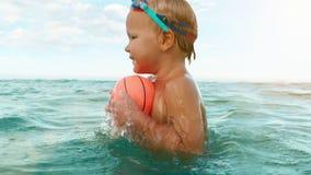 Ευτυχή παιχνίδια αγοριών με τη σφαίρα στη θάλασσα σε αργή κίνηση απόθεμα βίντεο