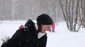 Ευτυχή παιχνίδια γυναικών με την λίγος γιος κατά τη διάρκεια των χιονοπτώσεων το χειμώνα απόθεμα βίντεο
