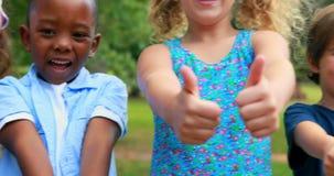 Ευτυχή παιδιά που εξετάζουν τη κάμερα με τους αντίχειρες επάνω απόθεμα βίντεο