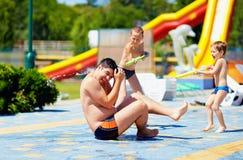 Ευτυχή παιδιά που καταβρέχουν το νερό στον πατέρα στο aquapark Στοκ φωτογραφία με δικαίωμα ελεύθερης χρήσης