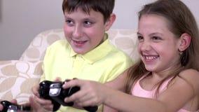 Ευτυχή παιδιά που παίζουν ένα τηλεοπτικό παιχνίδι απόθεμα βίντεο