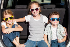 Ευτυχή παιδιά που παίρνουν έτοιμα για το οδικό ταξίδι μια ηλιόλουστη ημέρα Στοκ Εικόνες