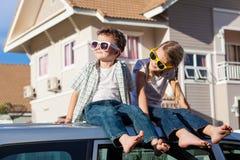 Ευτυχή παιδιά που παίρνουν έτοιμα για το οδικό ταξίδι μια ηλιόλουστη ημέρα Στοκ Φωτογραφίες