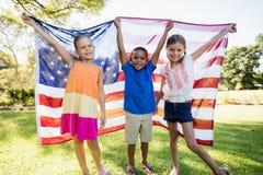 Ευτυχή παιδιά που παρουσιάζουν αμερικανική σημαία Στοκ Εικόνες