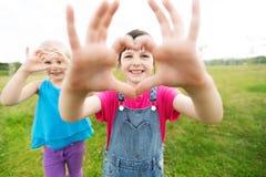 Ευτυχή παιδιά που παρουσιάζουν σημάδι μορφής καρδιών υπαίθρια Στοκ Εικόνες