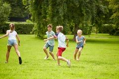 Ευτυχή παιδιά που τρέχουν και που παίζουν το παιχνίδι υπαίθρια Στοκ Εικόνες