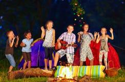 Ευτυχή παιδιά που χορεύουν γύρω από την πυρά προσκόπων Στοκ φωτογραφία με δικαίωμα ελεύθερης χρήσης