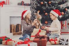 Ευτυχή παιδιά στα καπέλα santa που τα χριστουγεννιάτικα δώρα Στοκ Εικόνες