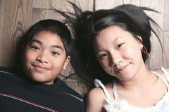 Ευτυχή παιδιά στο πάτωμα που βάζει στο ξύλινο πάτωμα Στοκ Φωτογραφίες