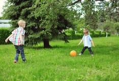 Ευτυχή παιδιά δύο αγόρια που παίζουν μαζί το ποδόσφαιρο με τη σφαίρα Στοκ Εικόνες