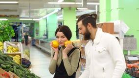 Ευτυχή πιπέρι και λαχανικό αγοράς ζευγών στο μανάβικο ή την υπεραγορά απόθεμα βίντεο