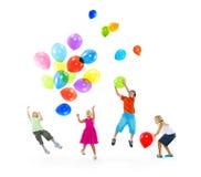 Ευτυχή πολυ-εθνικά παιδιά που παίζουν τα μπαλόνια από κοινού Στοκ Εικόνα