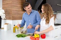 Ευτυχή τέμνοντα λαχανικά ζευγών και κατασκευή της σαλάτας Στοκ Εικόνες