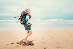 Ευτυχή ταξιδιωτικά τρεξίματα κοριτσιών backpacker χωρίς παπούτσια στην άμμο ωκεάνιο β στοκ φωτογραφία