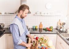 Ευτυχή τεμαχίζοντας λαχανικά ατόμων χαμόγελου για να κάνει τη σαλάτα Στοκ Φωτογραφία