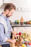 Ευτυχή τεμαχίζοντας λαχανικά ατόμων χαμόγελου για να κάνει τη σαλάτα Στοκ Εικόνες