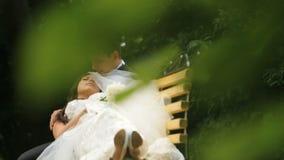 Ευτυχή υπόλοιπα newlyweds στον πάγκο στο πράσινο ηλιόλουστο πάρκο Ο νεόνυμφος αγγίζει στοργικά το πρόσωπο της νέας συζύγου του φιλμ μικρού μήκους
