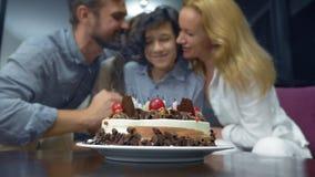 Ευτυχή φυσώντας κεριά αγοριών χαμόγελου στο κέικ γενεθλίων της παιδιά που περιβάλλονται από την οικογένειά τους birthday cake can απόθεμα βίντεο