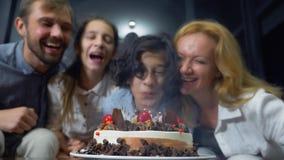 Ευτυχή φυσώντας κεριά αγοριών χαμόγελου στο κέικ γενεθλίων της παιδιά που περιβάλλονται από την οικογένειά τους birthday cake can στοκ φωτογραφίες