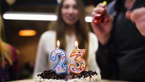 Ευτυχή φυσώντας κεριά κοριτσιών χαμόγελου έξω στο κέικ γενεθλίων της φιλμ μικρού μήκους