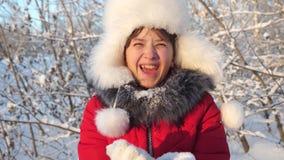 Ευτυχή φυσώντας snowflakes κοριτσιών εφήβων στο ηλιοβασίλεμα και χαμόγελο στο χειμερινό πάρκο κίνηση αργή το νέο κορίτσι φυσά sno φιλμ μικρού μήκους