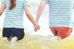 Ευτυχή χέρια εκμετάλλευσης ζευγών στην παραλία, το ταξίδι και την έννοια Relex στοκ φωτογραφίες με δικαίωμα ελεύθερης χρήσης