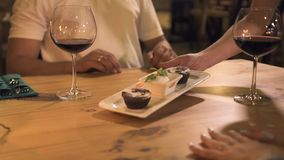 Ευτυχή χέρια εκμετάλλευσης ζευγών στον πίνακα με τα κεριά και γυαλί κρασιού στη ρομαντική ημερομηνία στο εστιατόριο Εκμετάλλευση  απόθεμα βίντεο