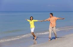 Ευτυχή χέρια εκμετάλλευσης ζεύγους τρέχοντας σε μια παραλία Στοκ εικόνα με δικαίωμα ελεύθερης χρήσης