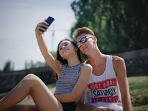 Ευτυχή χαμογελώντας αγόρι και κορίτσι σε ένα υπόβαθρο πάρκων Φίλος και φίλη που παίρνουν τις εικόνες Προοδευτική έννοια νεολαίας Στοκ Φωτογραφία