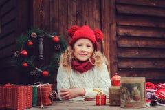 Ευτυχή Χριστούγεννα εορτασμού κοριτσιών παιδιών υπαίθρια στο άνετο ξύλινο εξοχικό σπίτι με τα δώρα Στοκ Εικόνες