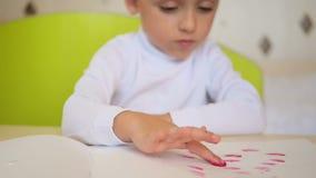 Ευτυχή χρώματα παιδιών με τα watercolors καθμένος στον πίνακα Το μικρό παιδί βάζει το δάχτυλό του στο χρώμα και τις κηλίδες φιλμ μικρού μήκους