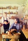 Ευτυχή artisans με τη ρόδα αγγειοπλαστικής και τα διάφορα σκάφη αργίλου Στοκ Εικόνες