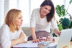 Ευτυχή madams που λειτουργούν με τον κατάλογο της παλέτας και του lap-top χρώματος Στοκ φωτογραφία με δικαίωμα ελεύθερης χρήσης