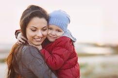 Ευτυχή mum και κοριτσάκι που περπατούν στην παραλία το φθινόπωρο Στοκ Φωτογραφίες