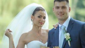 Ευτυχή newlyweds ερωτευμένα στο πάρκο ευτυχής εκλεκτής ποιότητας γάμος ημέρας ζευγών ιματισμού φιλμ μικρού μήκους