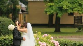 Ευτυχή newlyweds που αγκαλιάζουν, στο πράσινο θερινό πάρκο Ο όμορφος νεόνυμφος αγκαλιάζει tenderly την καλή νύφη του φιλμ μικρού μήκους