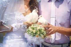 Ευτυχή newlyweds που κρατούν τα άσπρα περιστέρια Στοκ Φωτογραφία