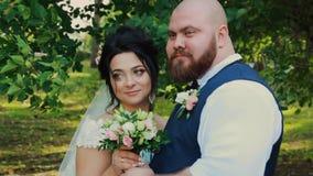 Ευτυχή newlyweds που περπατούν, αγκάλιασμα, που φιλά στο πάρκο φιλμ μικρού μήκους