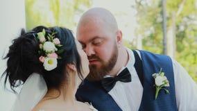 Ευτυχή newlyweds που περπατούν, αγκάλιασμα, που φιλά στο πάρκο απόθεμα βίντεο