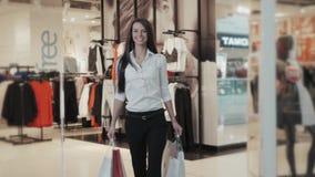 Ευτυχία, καταναλωτισμός, πώληση και έννοια ανθρώπων - χαμογελώντας νέα γυναίκα με τις τσάντες αγορών πέρα από το σπουδαστή υποβάθ απόθεμα βίντεο